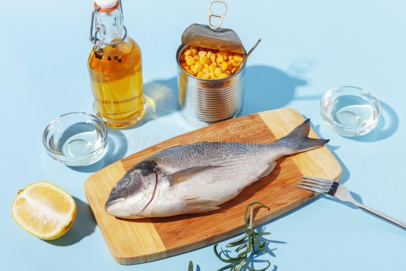 Ruwe doradovissen op een houten raad, ingredi?nten voor het koken en kruiden op een blauwe achtergrond royalty-vrije stock afbeeldingen