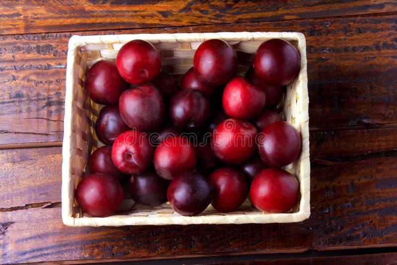 Ruwe en verse organische pruimen binnen rustieke stoffen houten vakje op rustieke lijst royalty-vrije stock afbeelding