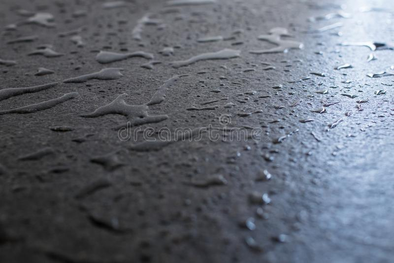 Ruwe en ruwe zwarte granietplak nat met water Dalingen en flard stock foto's