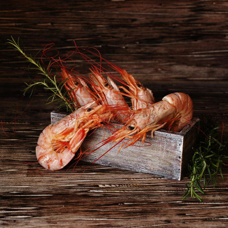 Ruwe of gekookte garnalen met rozemarijn in een houten doos stock foto