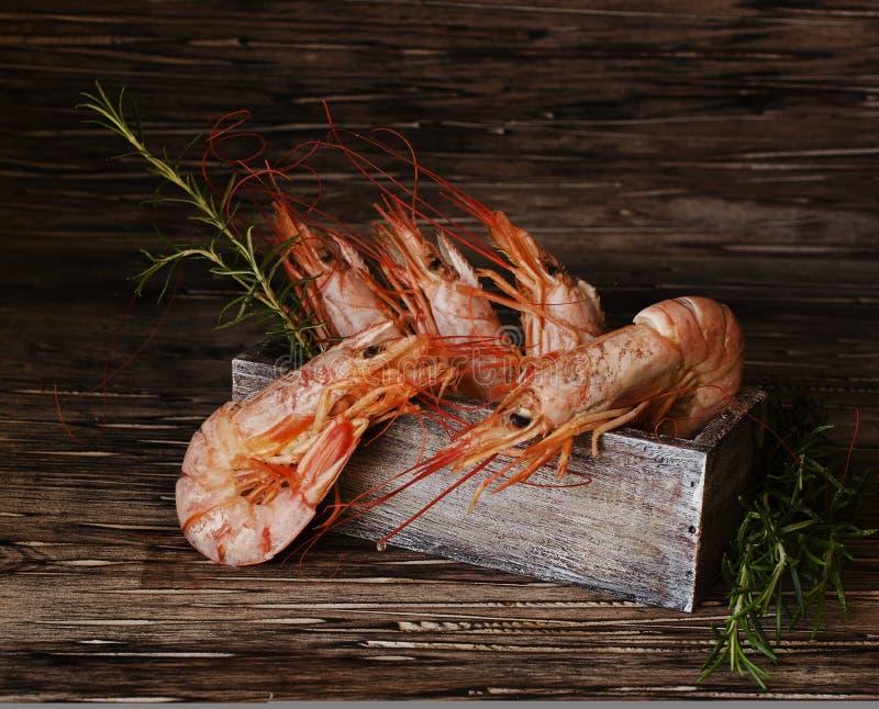 Ruwe of gekookte garnalen met rozemarijn in een houten doos stock afbeeldingen
