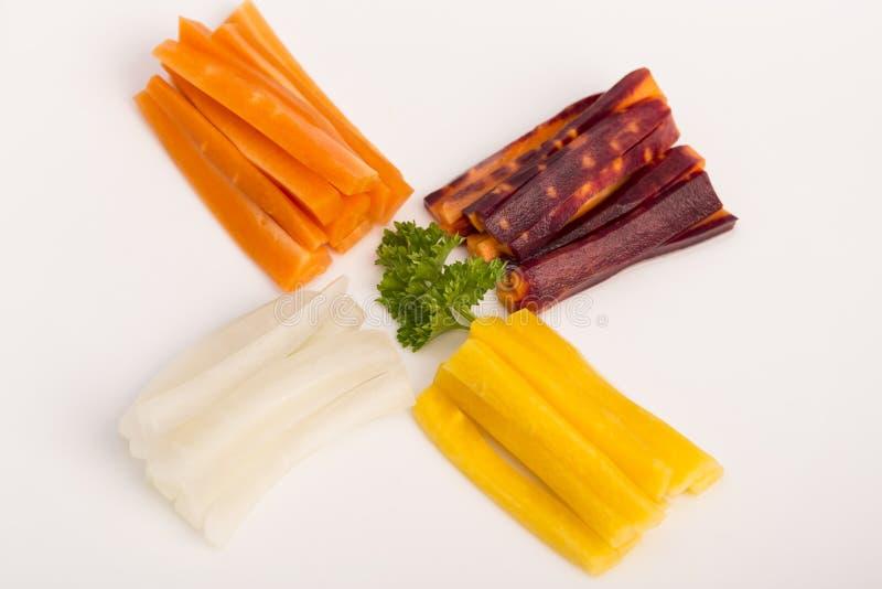 Ruwe gele, witte, oranje, rode wortelen stock foto