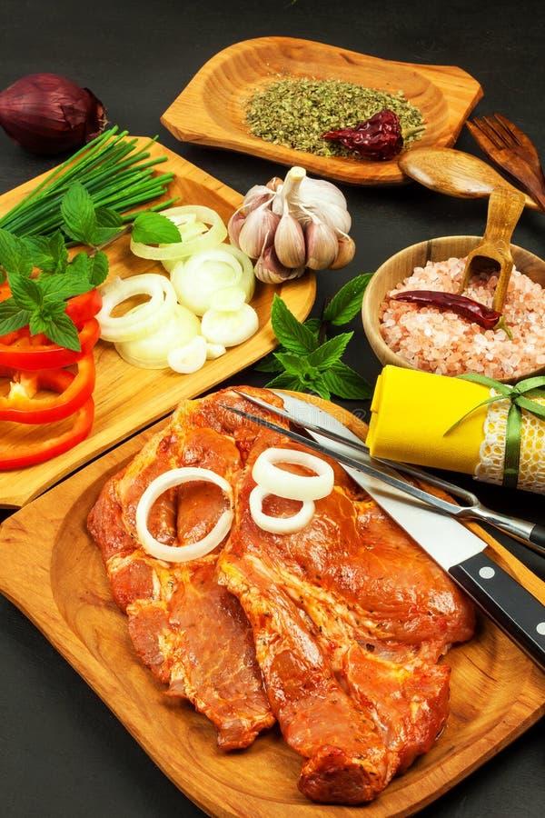 Ruwe gemarineerde varkensvleeshals Voorbereiding van vlees voor het roosteren Ruwe varkensvleesvlees en kruiden Vers vlees van ee stock afbeeldingen