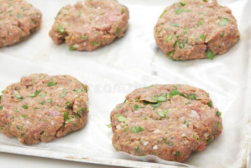 Ruwe hamburgerpasteitjes stock afbeeldingen
