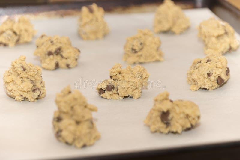 Ruwe het deegballen van het chocoladeschilferkoekje klaar om in o worden gebakken stock afbeelding