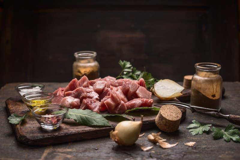 Ruwe ingrediënten voor goelasj of hutspot de ruwe kruiden van vleeskruiden op oude scherpe raad op rustieke houten achtergrond stock fotografie