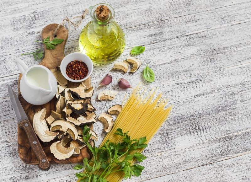 Ruwe ingrediënten voor het koken van deegwaren met porcinipaddestoelen - droge porcini schiet, spaghetti, room, knoflook, peterse stock fotografie