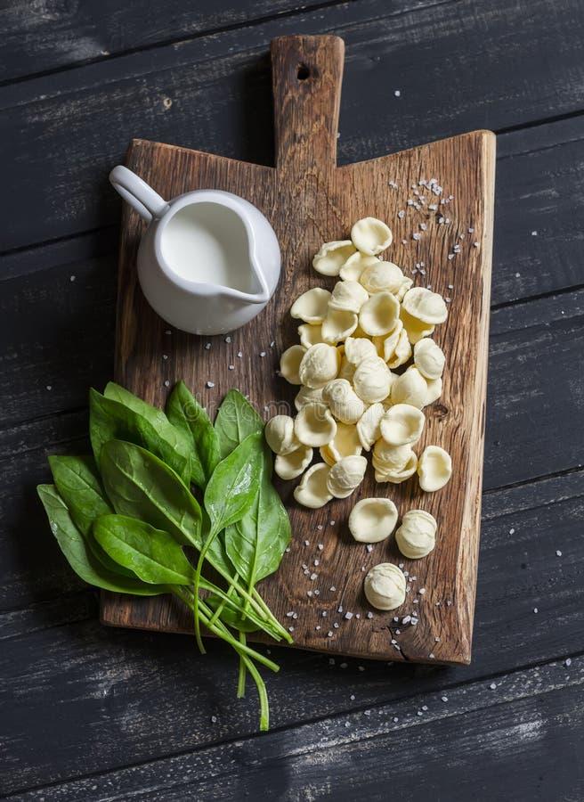 Ruwe ingrediënten voor het maken van deegwaren met spinazie saus afromen - orecchiettedeegwaren, verse spinazie, room royalty-vrije stock afbeelding