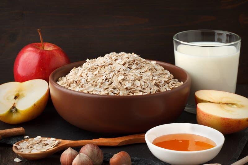 Ruwe ingrendients voor gezond ontbijtstilleven van haver schilfert in de kom, appel, melk, honing af stock afbeeldingen