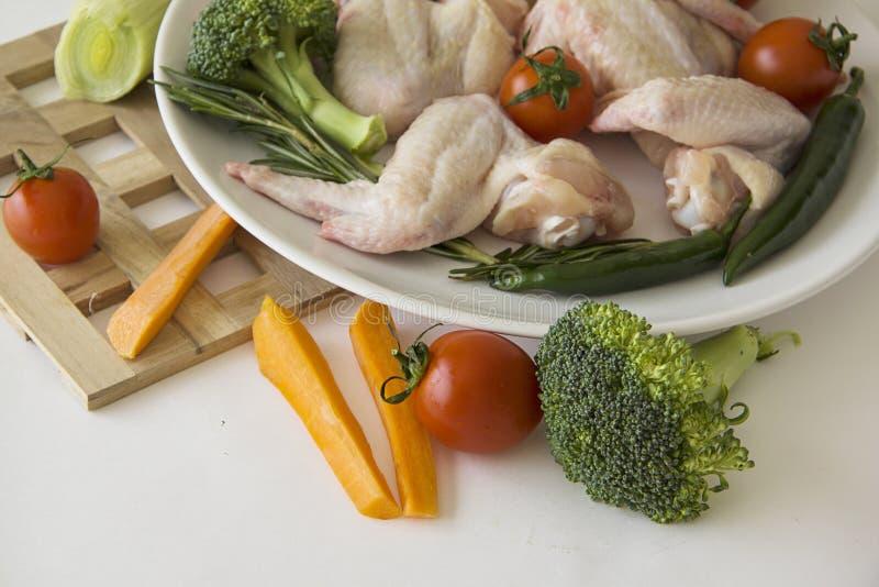 Ruwe kippenclose-up met wortelen en broccoli royalty-vrije stock foto's