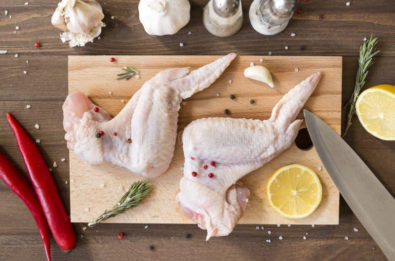 Ruwe kippenvleugels met kruiden op Hakbord, Spaanse peper, citroen, knoflook, rozemarijn, mes royalty-vrije stock afbeeldingen
