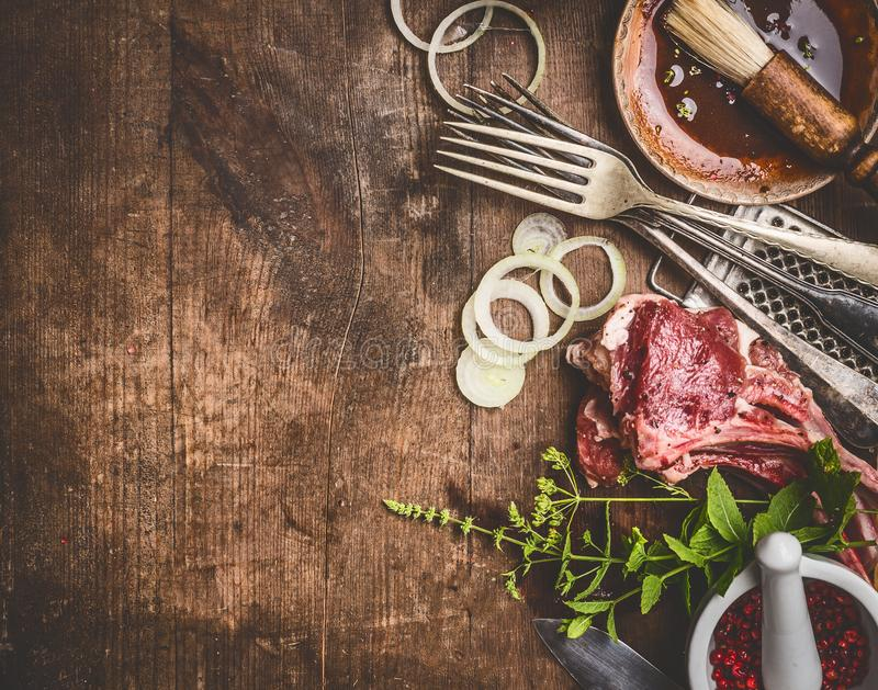 Ruwe lamsribben en grill of BBQ saus met keukengereikeukengerei met kruiden op houten achtergrond, hoogste mening stock afbeelding