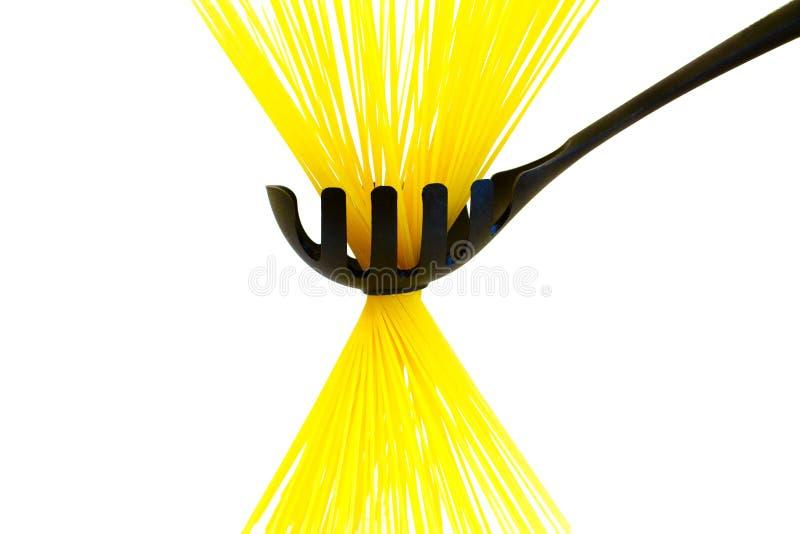 Ruwe lange gele spaghetti in de zwarte die lepel op wit wordt geïsoleerd royalty-vrije stock afbeeldingen
