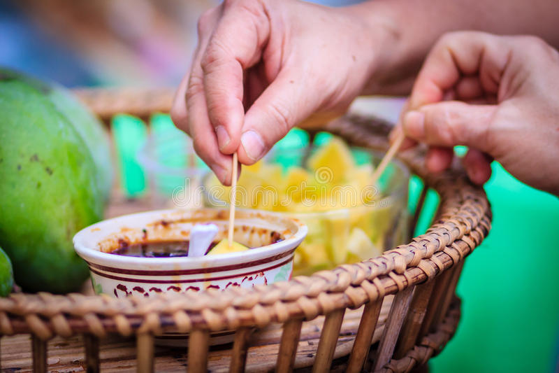 Ruwe Mangospaanders met zoete vissensaus voor verkoop in het lokale teken stock afbeeldingen