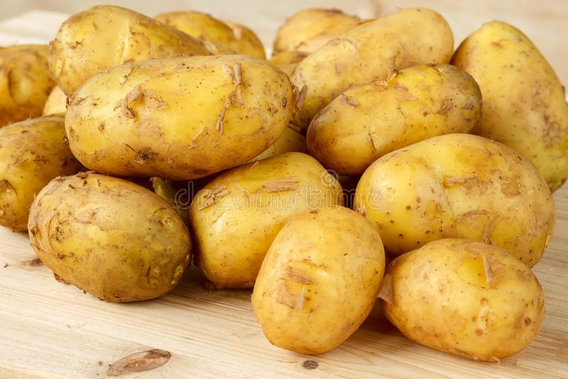 Ruwe nieuwe aardappels met schil op een houten achtergrond royalty-vrije stock fotografie