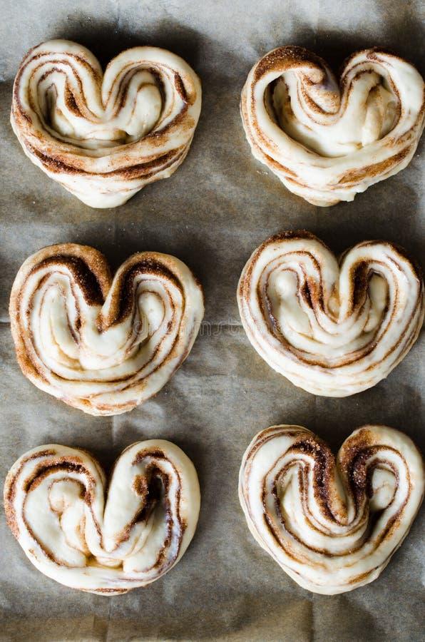 Ruwe ongebakken broodjes De broodjes van het gistdeeg met suiker en kaneel op bakseldocument, close-up stock foto's