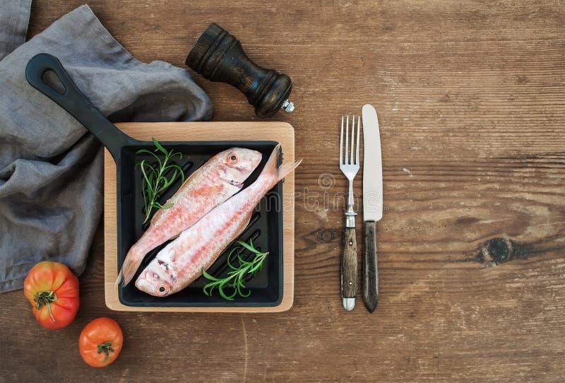 Ruwe ongekookte Mulvissen in een kokende pan met rozemarijn, citroen en knoflook over rustieke houten achtergrond stock foto's