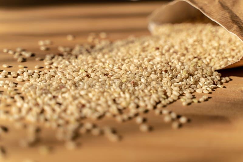 Ruwe Ongepelde rijst op de houten lijst van A met Zak op de Achtergrond r stock fotografie