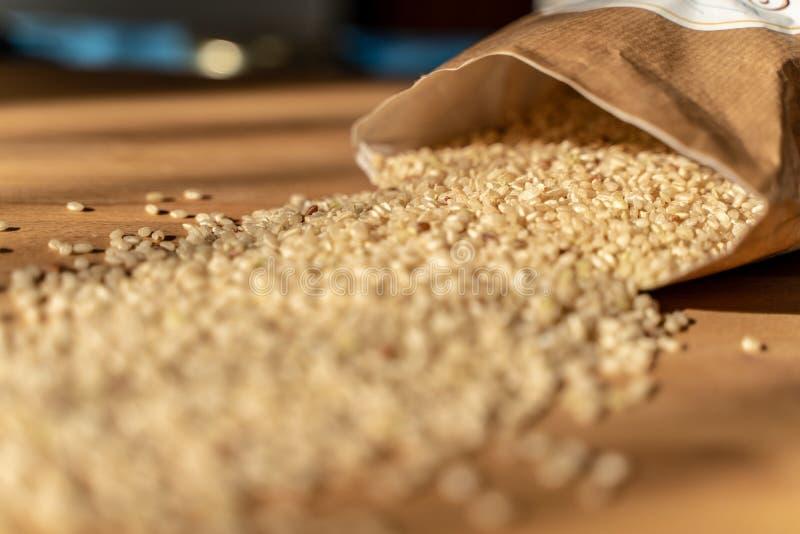 Ruwe Ongepelde rijst op de houten lijst van A met Zak op de Achtergrond r royalty-vrije stock afbeeldingen
