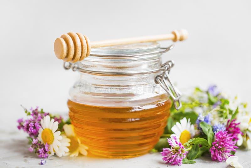 Ruwe organische honingskruik met bloemen stock afbeeldingen