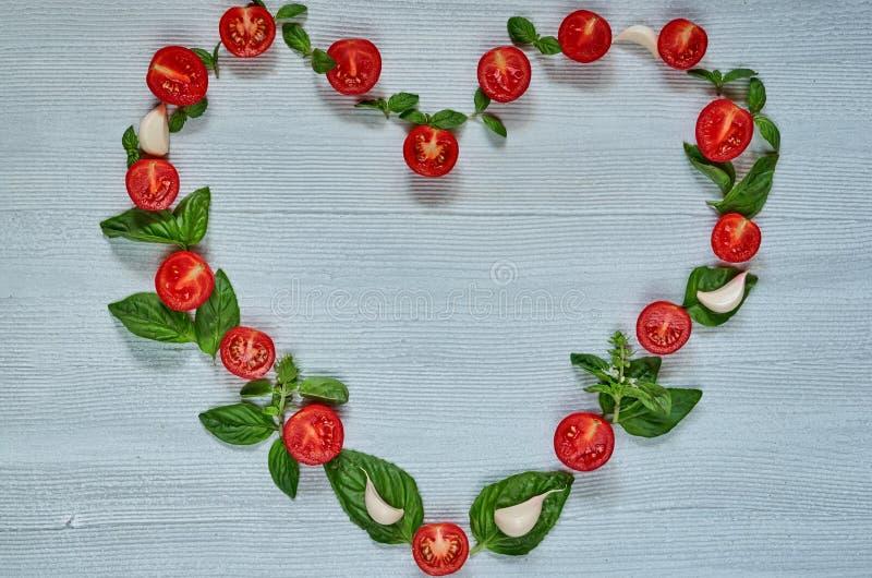 Ruwe organische ingrediënten voor caprese salade of gezonde vegetarische dieetschotel Kersentomaten, verse basilicumbladeren, kno stock afbeeldingen