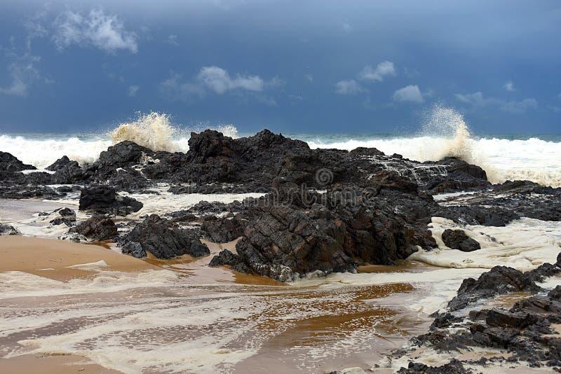 Ruwe overzees die over rotsen dichtbij kust breken royalty-vrije stock foto