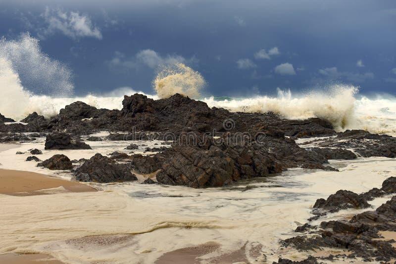 Ruwe overzees die over rotsen dichtbij kust breken stock fotografie