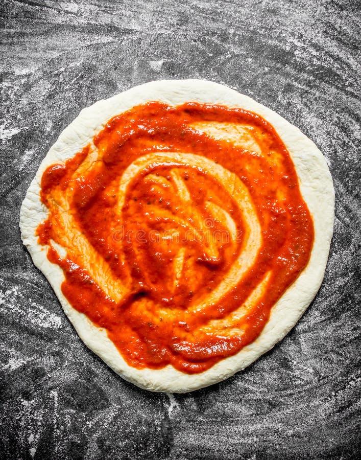 Ruwe pizza Ontwikkeld deeg met tomatenpuree royalty-vrije stock foto