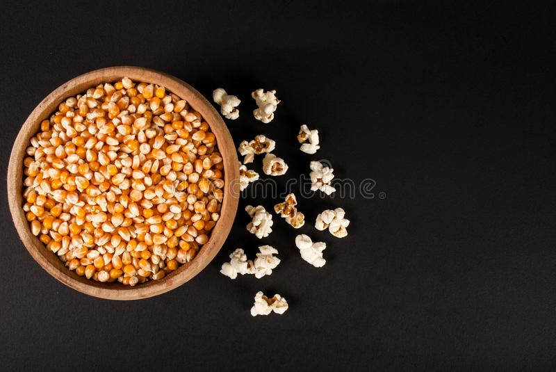 Ruwe popcorn in houten kom op zwarte achtergrond en ruimte voor tekst, hoogste mening stock fotografie