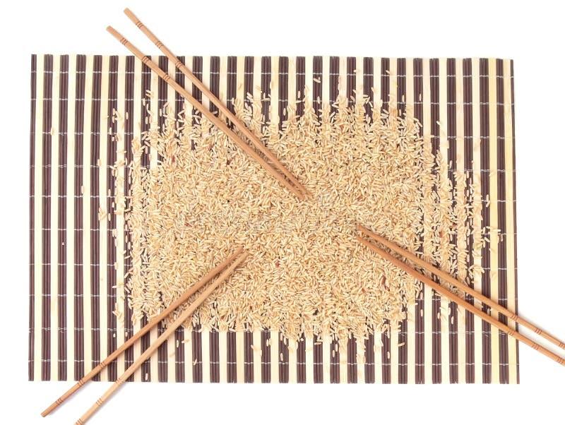 Ruwe rijst en eetstokjes op bamboetapijt royalty-vrije stock foto's
