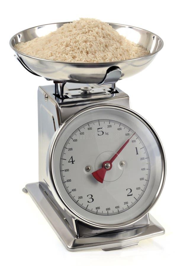 Ruwe rijst op dichte omhooggaand van de keukenschaal op witte achtergrond royalty-vrije stock afbeeldingen