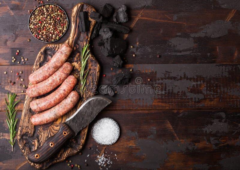 Ruwe rundvlees en varkensvleesworst op oud hakbord met uitstekend mes op donkere houten achtergrond Zout en peper met rozemarijn  royalty-vrije stock fotografie