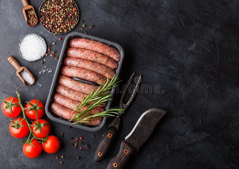Ruwe rundvlees en varkensvleesworst in plastic dienblad met uitstekend mes en vork op zwarte achtergrond Zout en peper met tomate royalty-vrije stock foto's