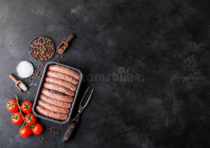 Ruwe rundvlees en varkensvleesworst in plastic dienblad met uitstekende vork op zwarte achtergrond Zout en peper met tomaten en r royalty-vrije stock afbeelding