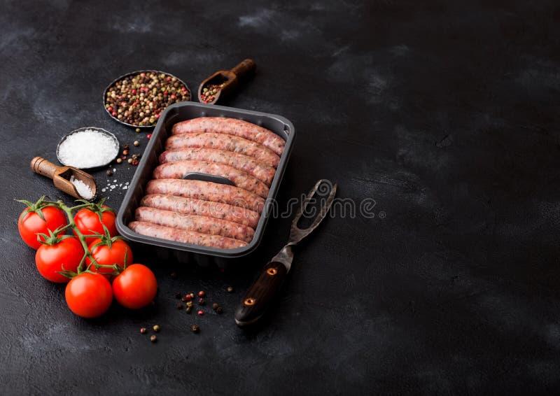 Ruwe rundvlees en varkensvleesworst in plastic dienblad met uitstekende vork op zwarte achtergrond Zout en peper met tomaten en r royalty-vrije stock fotografie