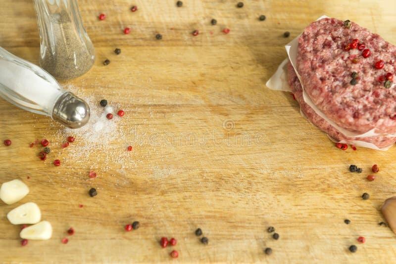 2 ruwe rundvleeslapjes vlees met kruiden op houten keukenraad, zout shak royalty-vrije stock fotografie