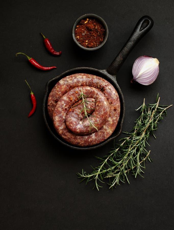 Ruwe rundvleesworsten op een gietijzer pan, selectieve nadruk royalty-vrije stock afbeeldingen