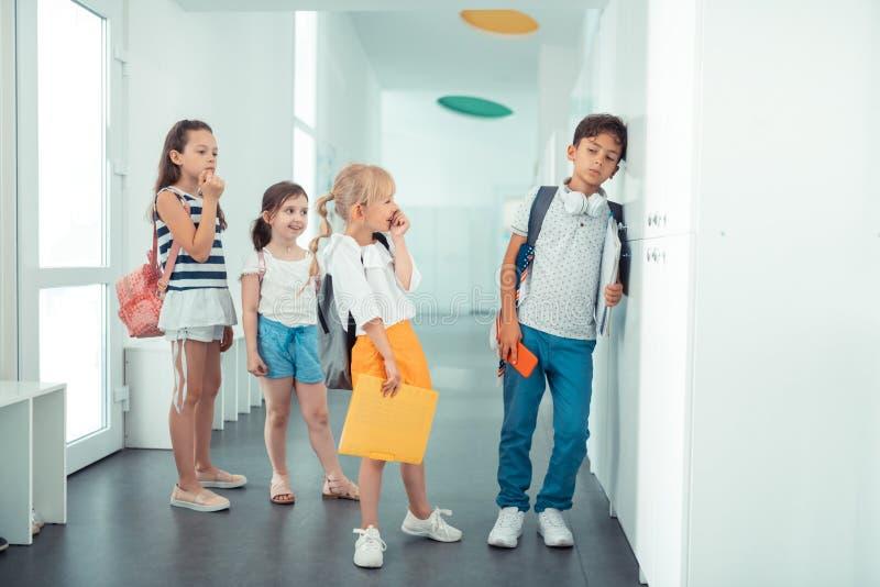 Ruwe schoolmeisjes die bij jongen droevig en eenzaam voelen lachen stock foto's