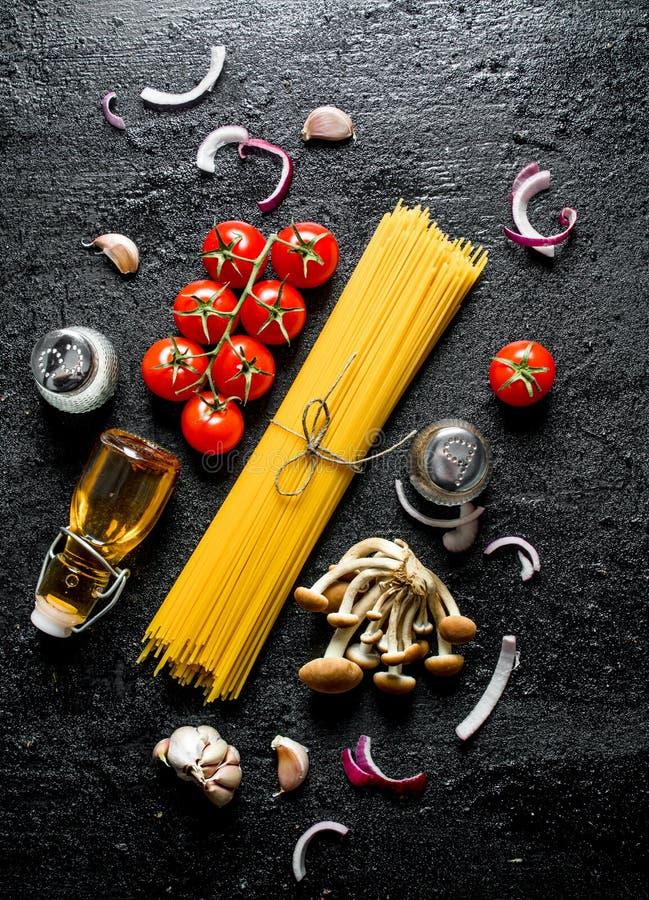 Ruwe spaghetti met uiplakken, tomaten, paddestoelen en olie in een fles royalty-vrije stock foto's