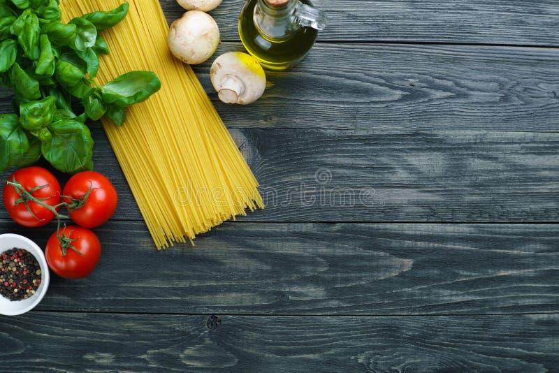 Ruwe spaghetti, tomaten, basilicum, olijfolie, paddestoelen en kruiden royalty-vrije stock afbeelding