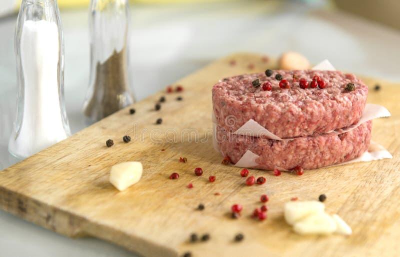2 ruwe varkensvleeslapjes vlees met kruiden op een houten Raad, zout, knoflook, peper, vlees, koteletten stock foto's