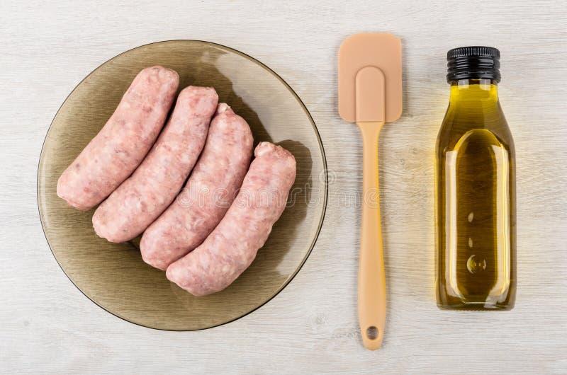 Ruwe varkensvleesworsten in plaat, spatel en fles olie royalty-vrije stock afbeeldingen