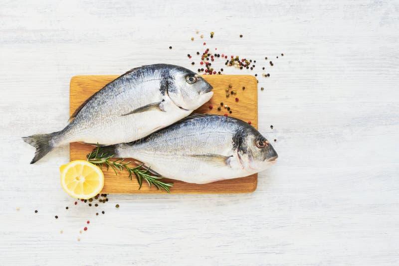 Ruwe verse doradavissen met kruiden op houten scherpe raad Gezond voedselconcept Hoogste mening, exemplaarruimte royalty-vrije stock foto's