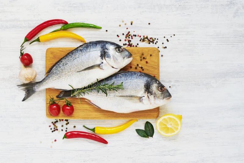 Ruwe verse doradavissen met kruiden op houten scherpe raad Gezond voedselconcept Hoogste mening, exemplaarruimte royalty-vrije stock foto