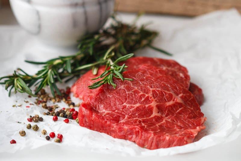 Ruwe verse lapjes vlees van het marmeren rundvlees, de rozemarijn en de kruiden stock foto's