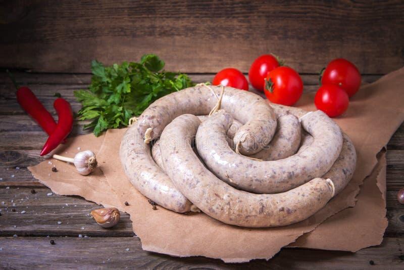 Ruwe verse witte worsten op een ambachtdocument met groenten r De traditionele Beierse of witte gemaakte worst van M?nchen royalty-vrije stock afbeelding