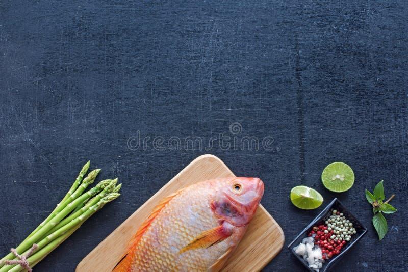 Ruwe vissen, asperge, kruiden en kruiden stock afbeelding