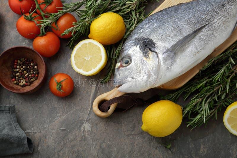 Ruwe vissen en tomaten op lei stock afbeelding