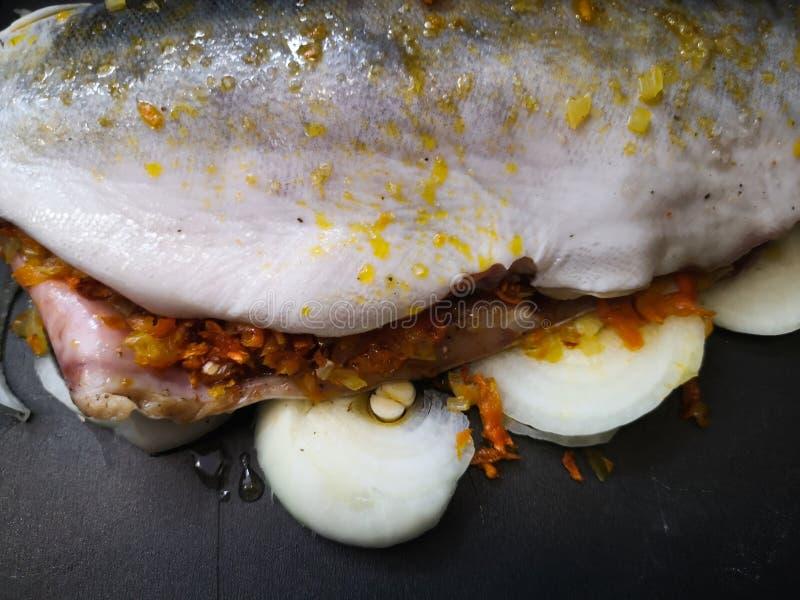 Ruwe vissen op het bakselblad Het koken gehele geroosterde vissenseriola met citroen die in de oven wordt gebakken De chef-kok ze stock foto