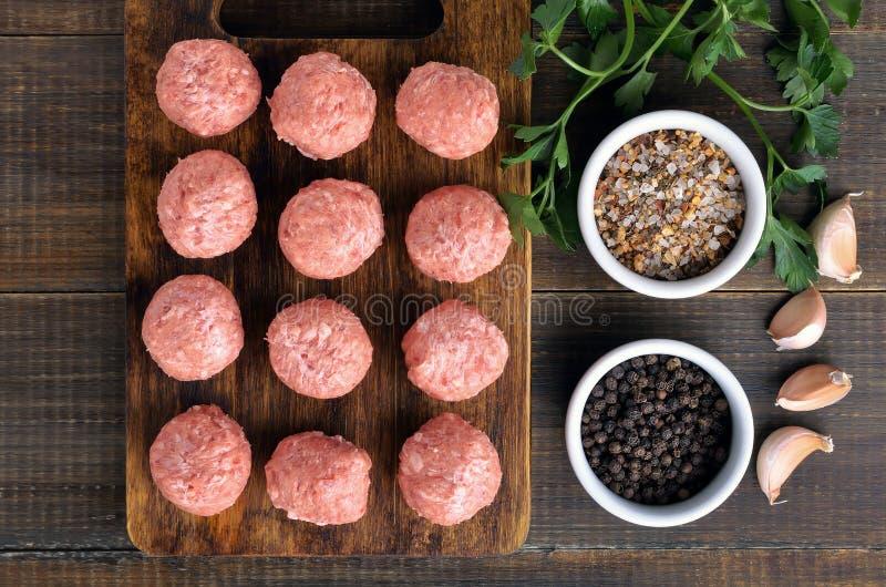 Ruwe vleesballetjes op de scherpe raad en de kruiden royalty-vrije stock afbeelding